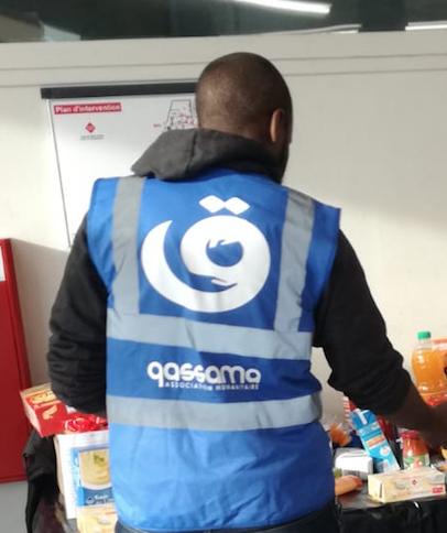 Samir de dos portant le gilet de l'association Qassama avec son logo