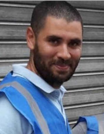 Samir souriant avec le gilet de bénévoles de Qassama