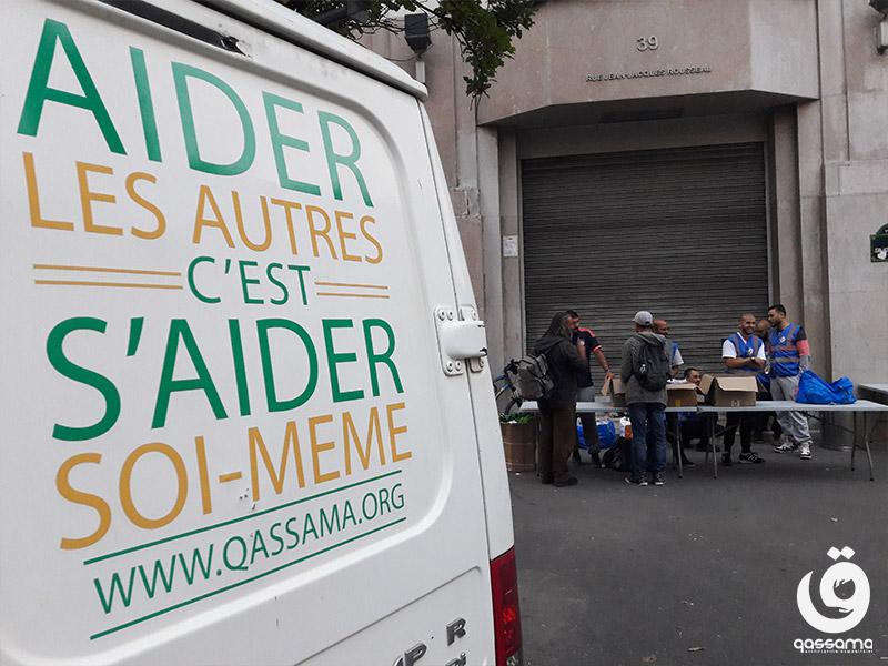 """Camionette avec le slogan de l'association, """"aider les autres c'est s'aider soi-même"""", devant un groupe de bénévoles et bénéficiaires"""